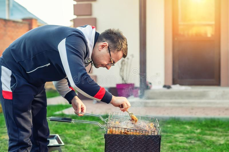 Male person preparing chicken wings on grill at open fire brazier. Barbecue  friens home party at house backyard. Weeken bbq stock photos