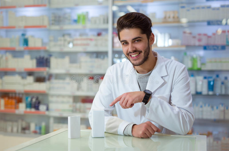 Male pharmacist dispensing medicine holding a box of ta stock images
