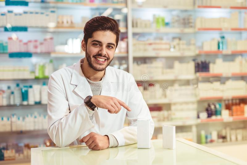 Male pharmacist dispensing medicine holding a box of tablets royalty free stock photography