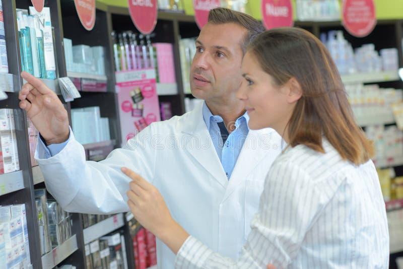 Male pharmacist helping female customer in store stock photo