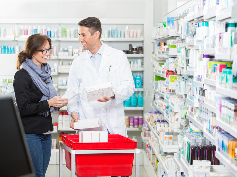 Male Pharmacist Showing Medicines To Female royalty free stock images
