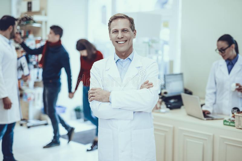 Pharmacists and customers in pharmacy. Male Pharmacist Smiling with Arm Crossed. Other Pharmacists with Customers on Background. Customers Choose a Medicaments royalty free stock images