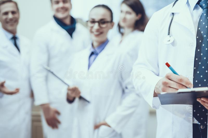 Pharmacists Posing in Pharmacy. Male Pharmacist is Writing Information about a Something. Blur View of Other Pharmacists on Background. Pharmacists is Wearing a royalty free stock image