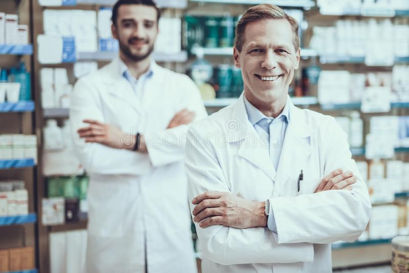 Male pharmacists posing in pharmacy. Three Pharmacists Posing. Pharmacists is a Caucasian Men and Young Woman. People Wearing a Special Medical Uniform. People stock image