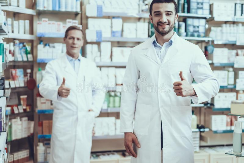 Male pharmacists posing in pharmacy. Two Pharmacists Looking into Camera. Pharmacists is a Caucasian Adult Man and Young Guy. Men Wearing a Special Medical royalty free stock photo