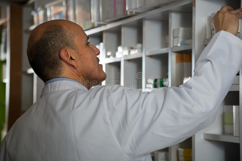 Male pharmacists working in farmacy. Portrait of male pharmacists working in modern farmacy stock image