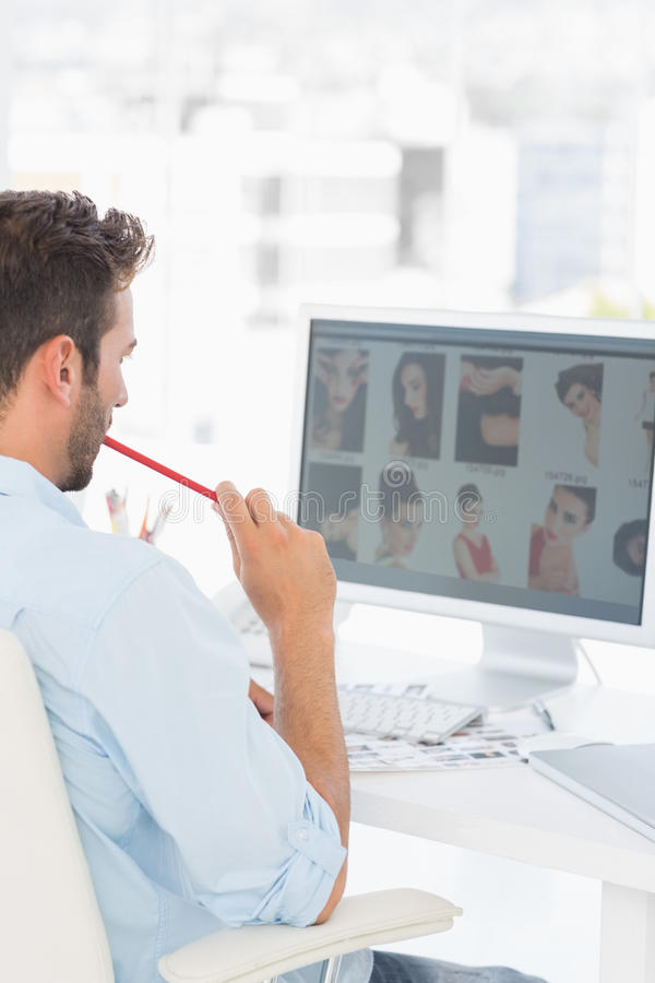 Male photo editor working on computer in office stock photo