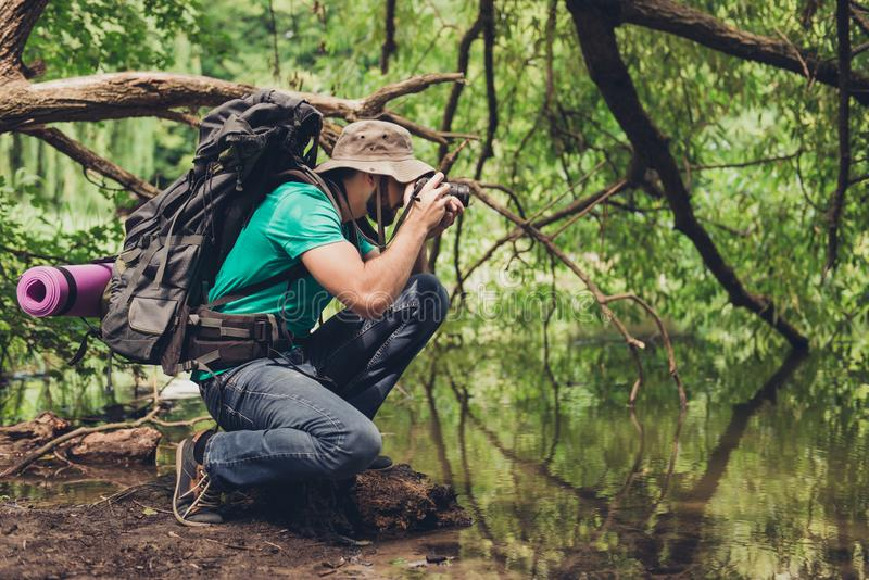 Male photographer is near the lake outdoors in the spring wood, taking shot of beautiful nature! He is a tourist, hiking in jungle. Handsome guy stock photo
