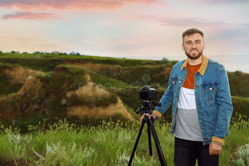 Male photographer with professional camera on hill royalty free stock image