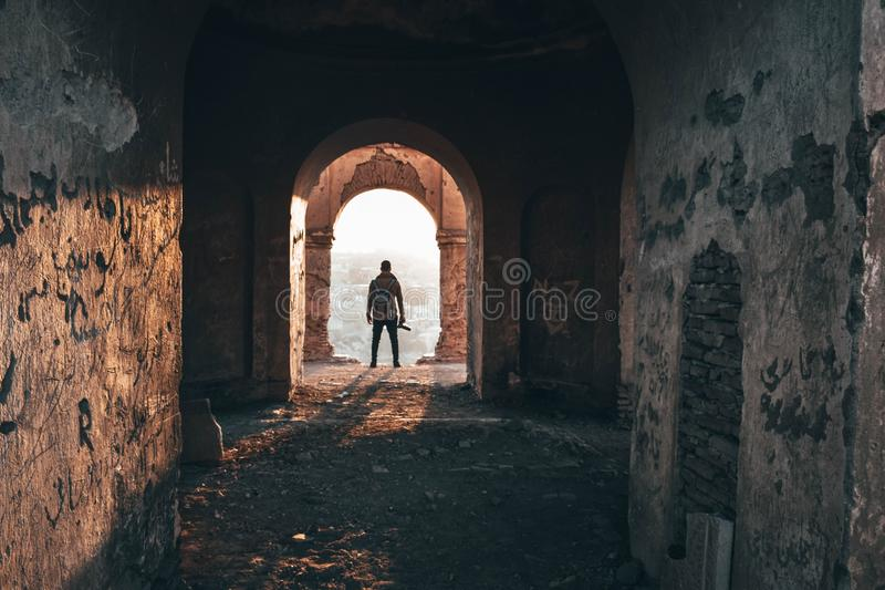 Male photographer standing in the archway of an old abandoned architecture royalty free stock photos