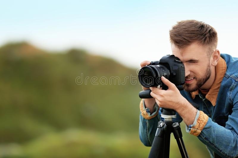 Male photographer taking picture of beautiful landscape with professional camera on green hill stock photo