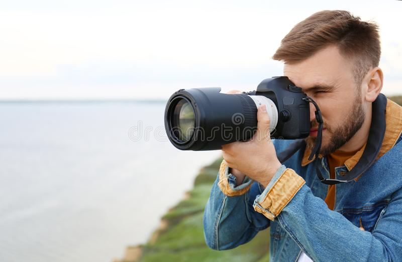 Male photographer taking picture of beautiful landscape with professional camera on green hill royalty free stock photo