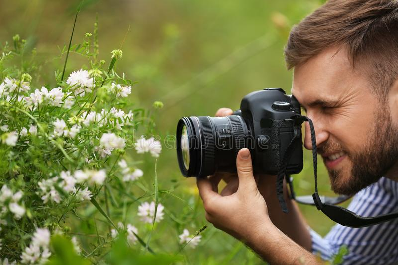 Male photographer taking picture of  plants with professional camera outdoors royalty free stock photography