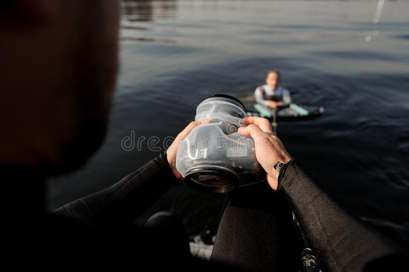 Male photographer taking pictures from the motorboat of the girl on the wake surf. Male photographer taking pictures with a camera in waterproof cover from the royalty free stock photography