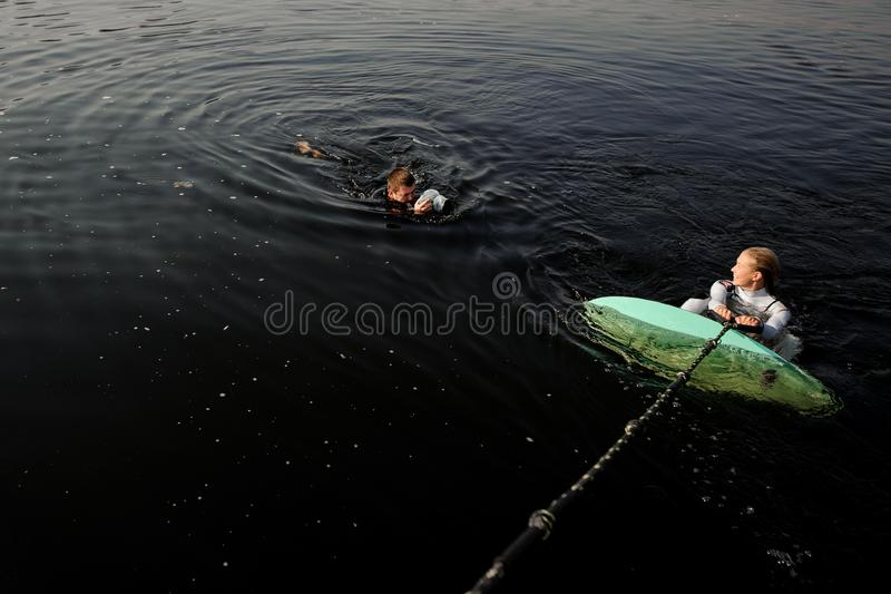 Male photographer taking pictures from the water of the girl with a wake surf. Male photographer taking pictures with a camera in waterproof cover from the water stock photo