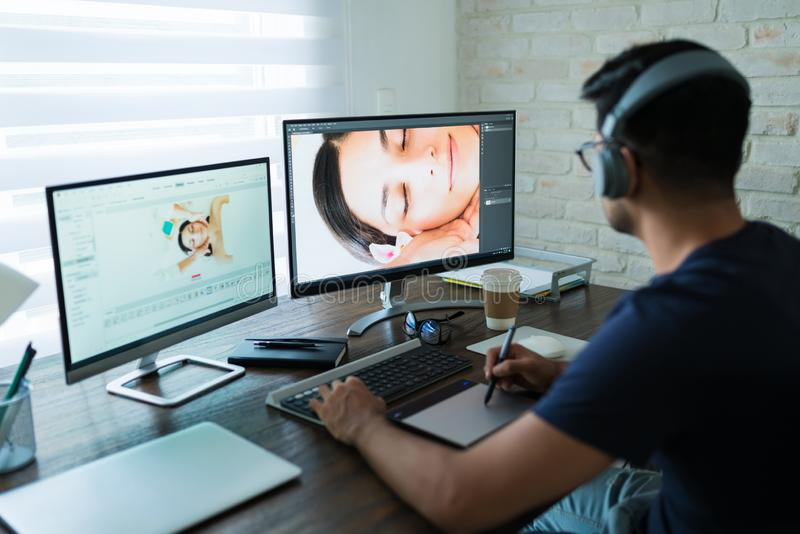 Young Freelancer Retouching While Working At Home stock images