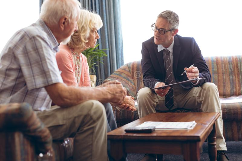 Male physician interacting with senior couple at retirement home. Front view of matured Caucasian male physician interacting with senior Caucasian couple at stock images