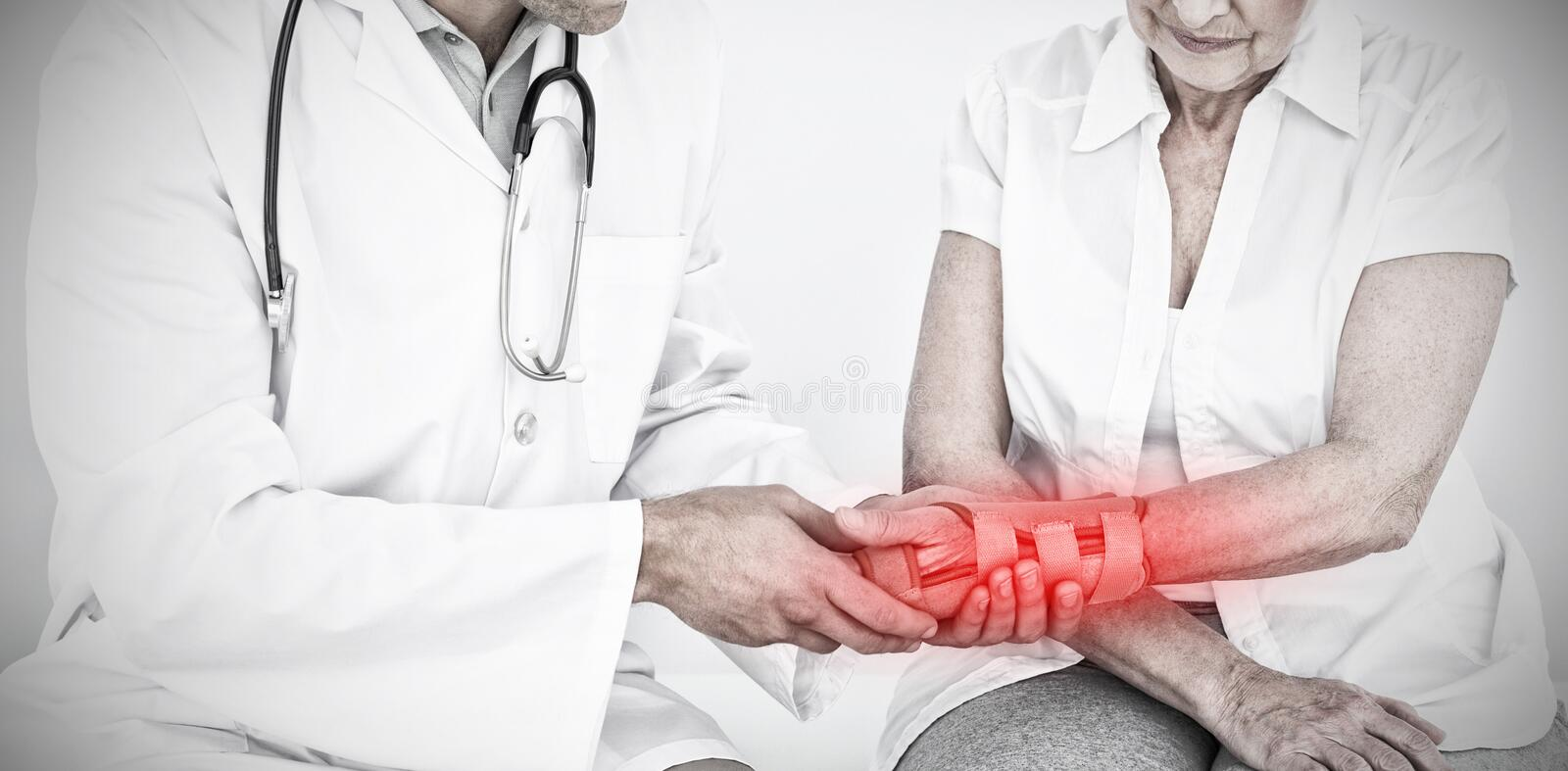 Composite image of male physiotherapist examining a senior womans wrist stock photo