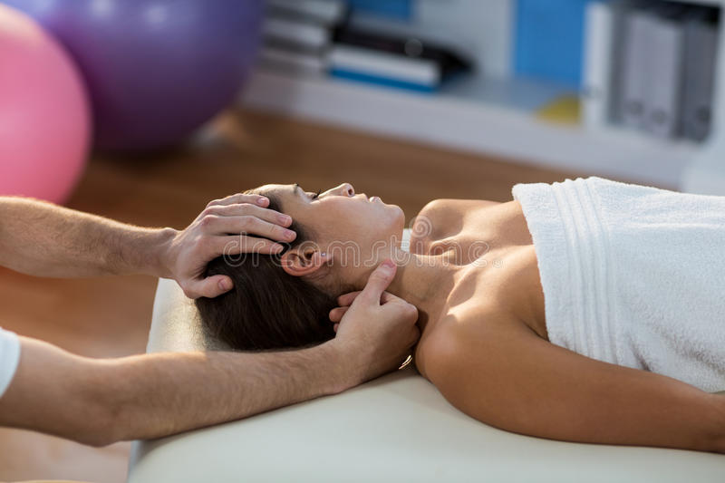Male physiotherapist giving head massage to female patient royalty free stock photography