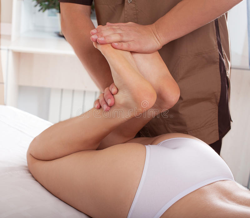 Male physiotherapist or orthopedist doing adjustment stock image