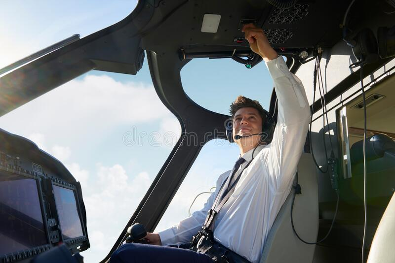 Male Pilot In Cockpit Of Helicopter Doing Pre Flight Check Before Take Off stock photos
