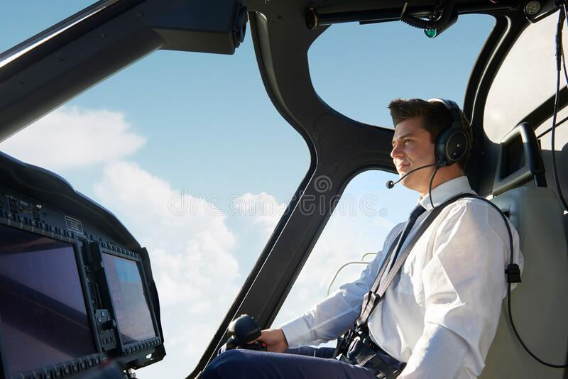 Male Pilot In Cockpit Of Helicopter During Flight stock photo