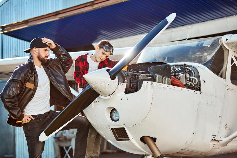 Male pilot and his son standing near opened engine block, searching for reason of failure stock photography