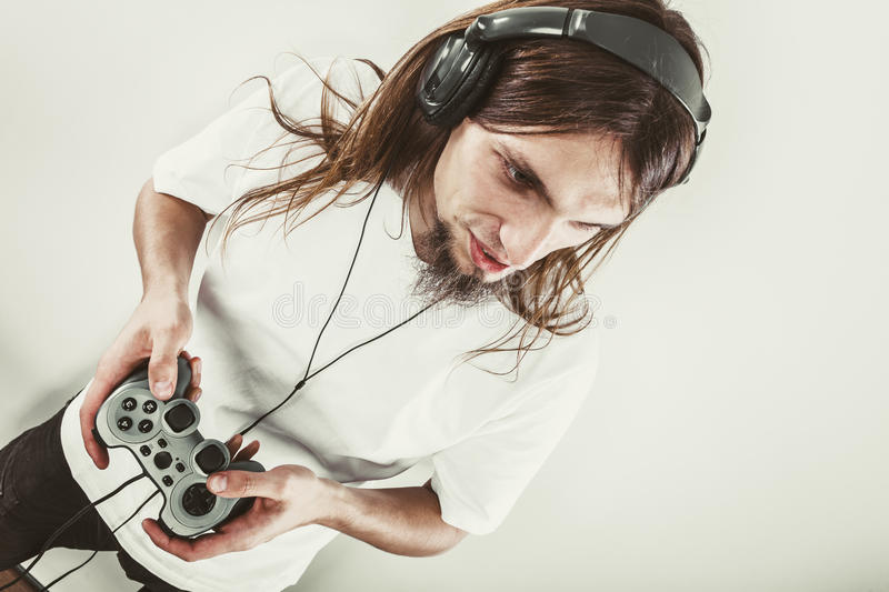 Male player focus on play games. Lifestyle of young people. Student man spending time on playing games videogames console playstation. Long haired guy focus on royalty free stock photo