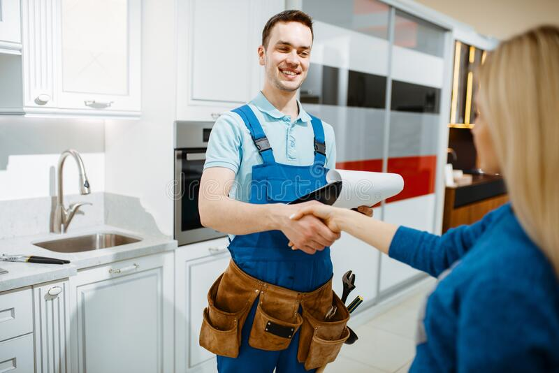 Male plumber and female customer in the kitchen royalty free stock photo