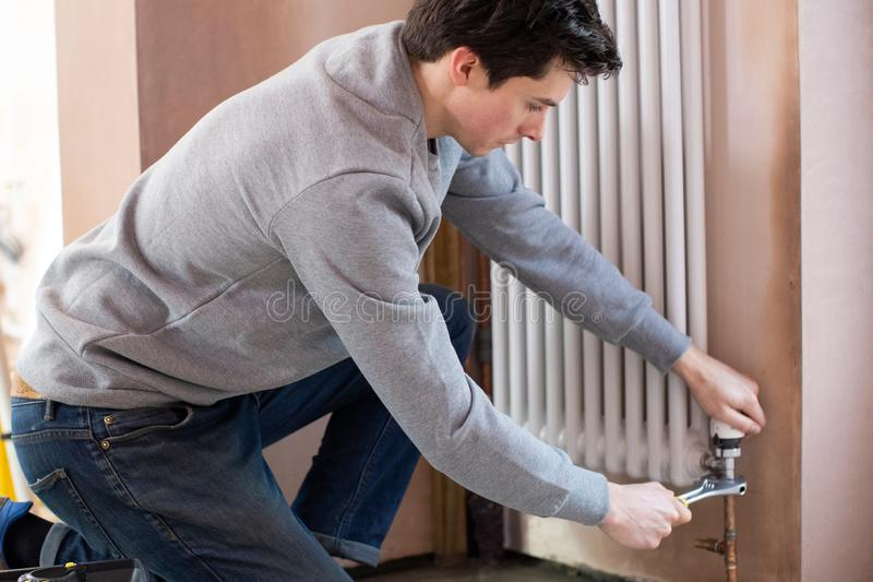 Male Plumber Fitting Vertical Radiator In Room Of House royalty free stock images