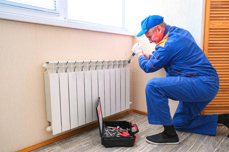 Male plumber fixes a leak. The adjustable wrench tighten the nut clamps seals, isolates stock images