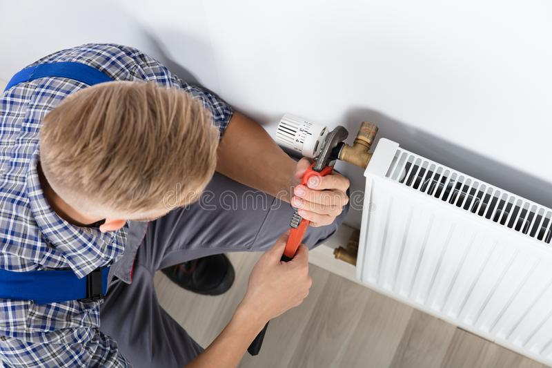 Male Plumber Fixing Thermostat Using Wrench royalty free stock photo