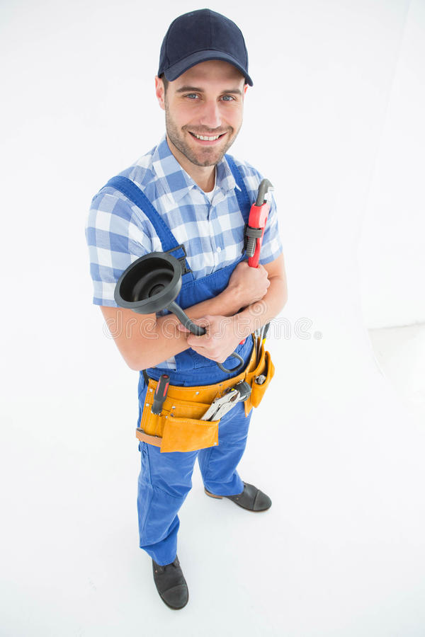 Male plumber holding plunger and wrench. Portrait of young male plumber holding plunger and wrench on white background stock photo