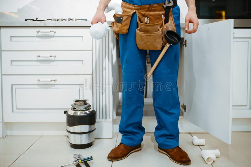 Male plumber installing water filter in kitchen royalty free stock photo