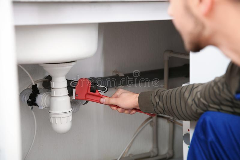 Male plumber repairing kitchen sink with pipe wrench stock photography