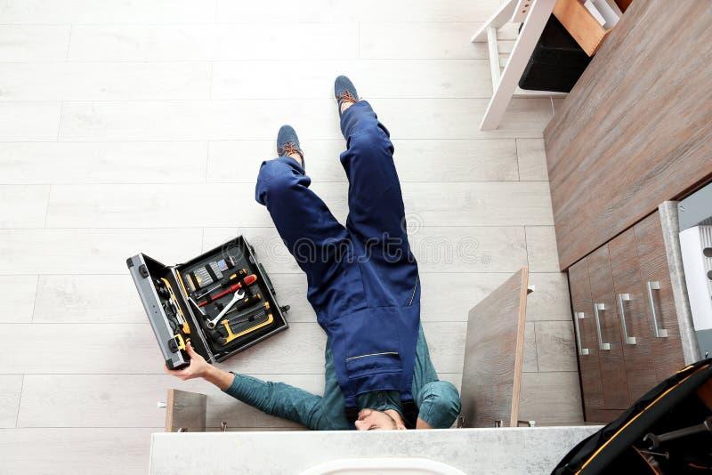 Male plumber repairing kitchen sink royalty free stock photos