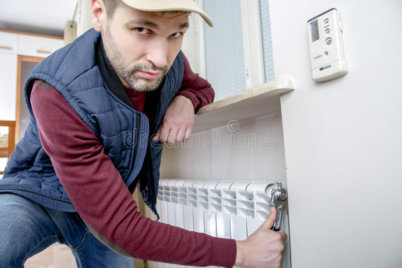 Male plumber repairing radiator with wrench. stock image