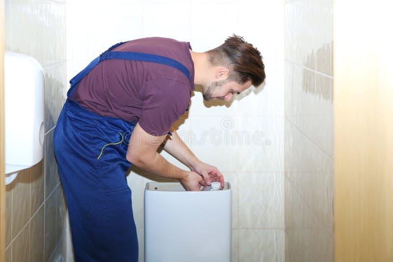 Male plumber repairing toilet tank royalty free stock photo