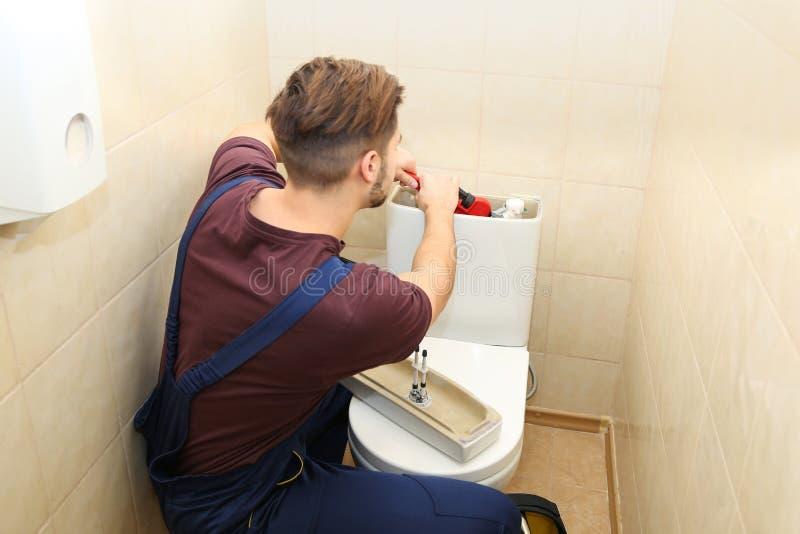 Male plumber repairing toilet tank in bathroom royalty free stock photography