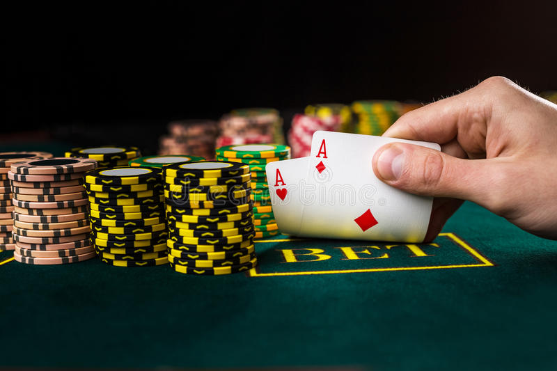 Male poker player lifting the corners of two cards aces. Close-up of male poker player lifting the corners of two cards aces at green casino table with aces stock images
