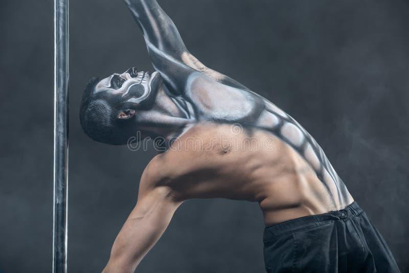 Male pole dancer posing in dark studio royalty free stock images