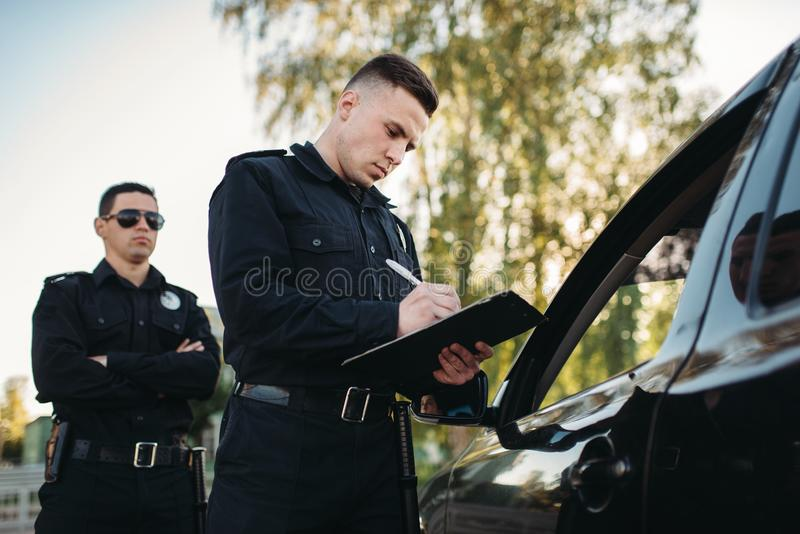 Male police officers check vehicle on the road. Male police officers in uniform check vehicle on the road. Law protection, car traffic inspector, safety control royalty free stock images