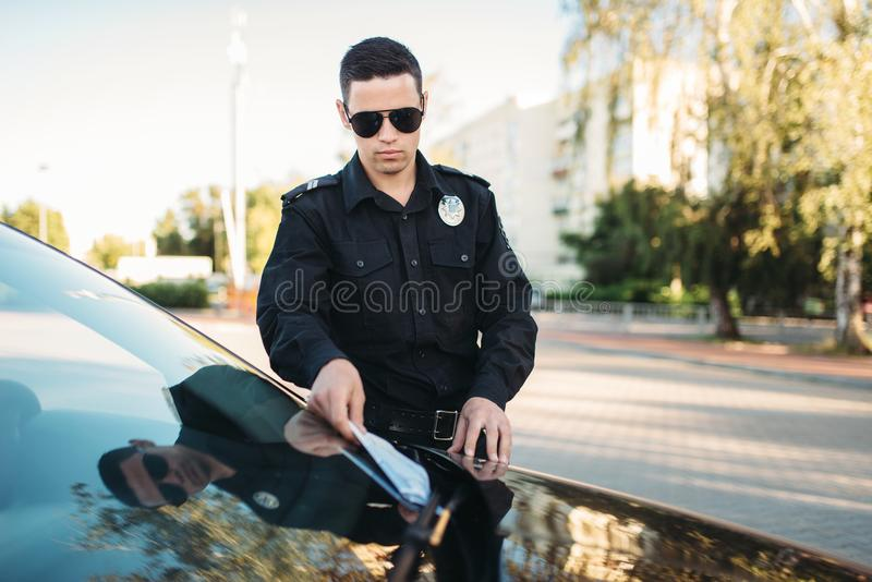 Male policeman in uniform writes a fine on road. Male policeman in uniform writes a fine on the road. Law protection, car traffic inspector, safety control job stock photos