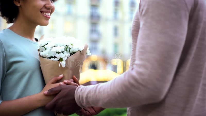 Male presenting flowers to pretty girlfriend, hugging on summer date, surprise stock photography