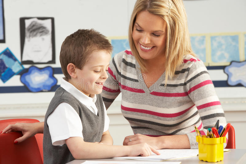 Male Primary School Pupil And Teacher Working stock image