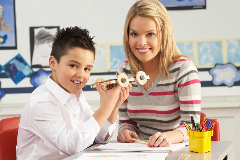 Male Primary School Pupil And Teacher Working royalty free stock photography
