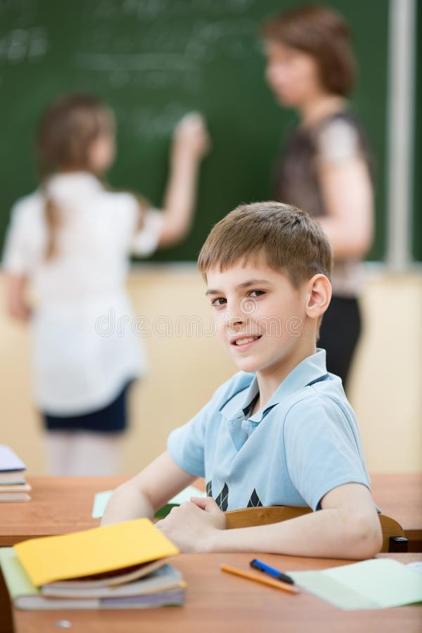 Male primary school student in classroom with classmate and teacher. Child primary school student in classroom with classmate and teacher royalty free stock image