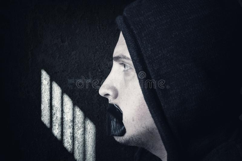 Male prisoner with hoodie and covered mouth by black tape stock photos