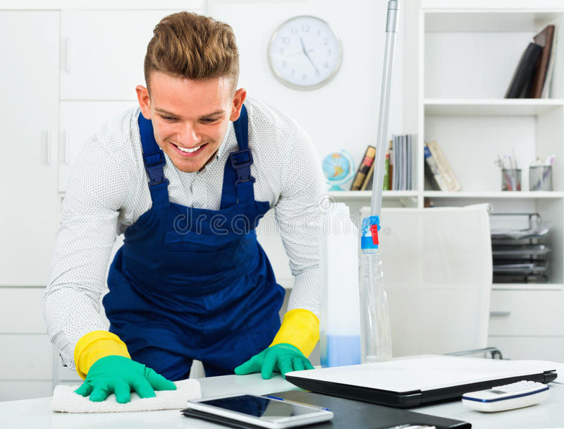 Male professional janitor dusting in office royalty free stock images