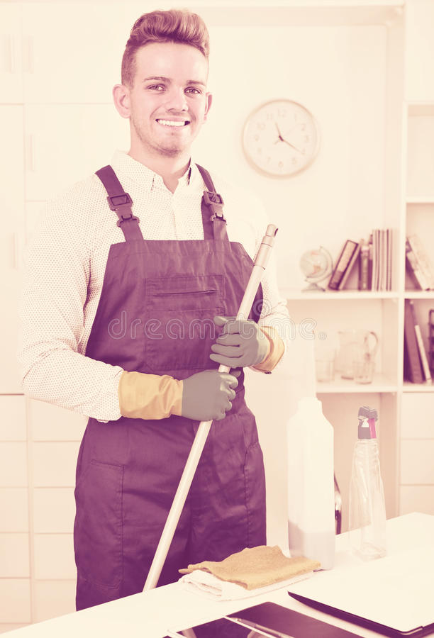 Male professional janitor dusting in office stock images